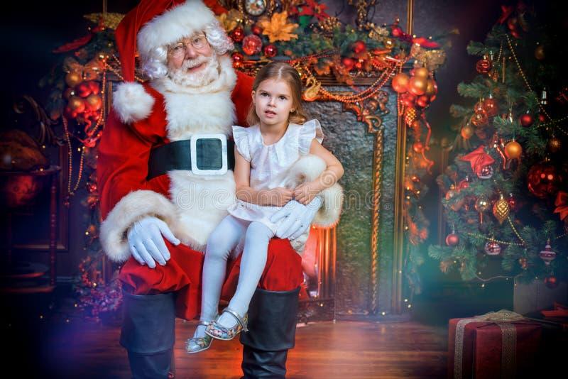 Santa que guarda uma menina fotos de stock