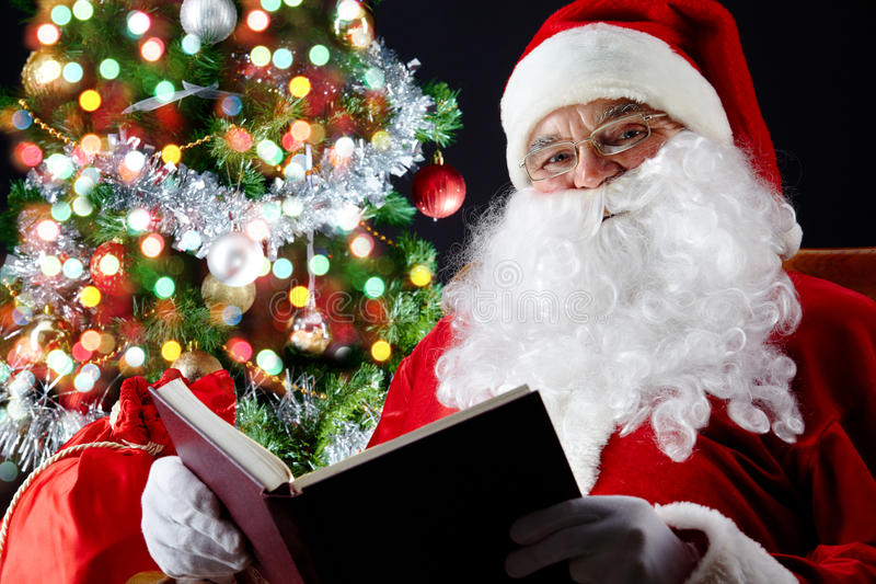 Santa que lee un libro imagen de archivo