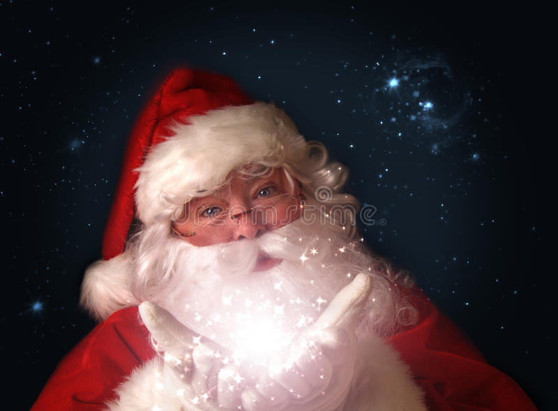 Santa que prende luzes de Natal mágicas nas mãos fotografia de stock royalty free
