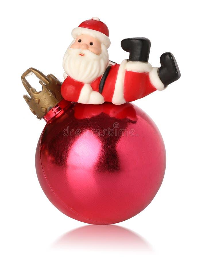 Santa que se reclina sobre una bola de la Navidad imagen de archivo