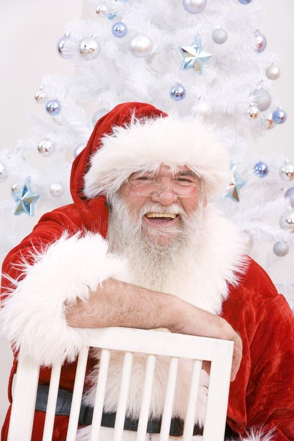 Santa que senta-se em uma cadeira imagens de stock