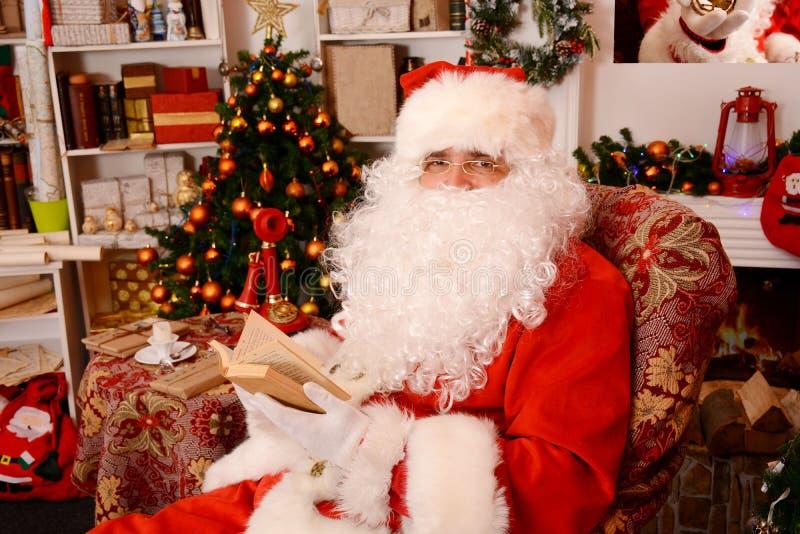 Santa que senta-se na árvore de Natal, perto da chaminé e lendo um livro foto de stock