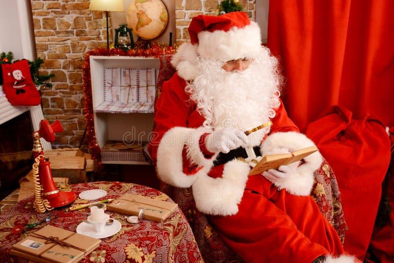 Santa que senta-se na árvore de Natal, perto da chaminé e lendo um livro imagens de stock royalty free