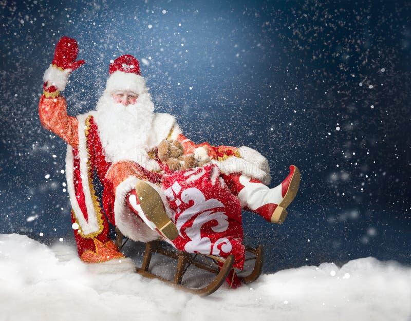 Santa que voa seu trenó contra a neve fotografia de stock