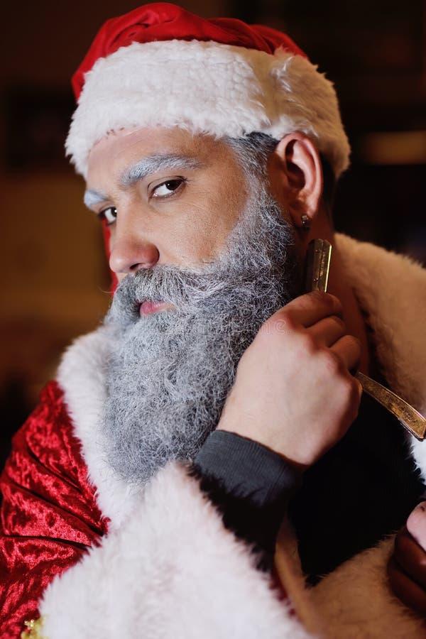 Santa rade la sua barba contro lo sfondo del parrucchiere immagine stock libera da diritti