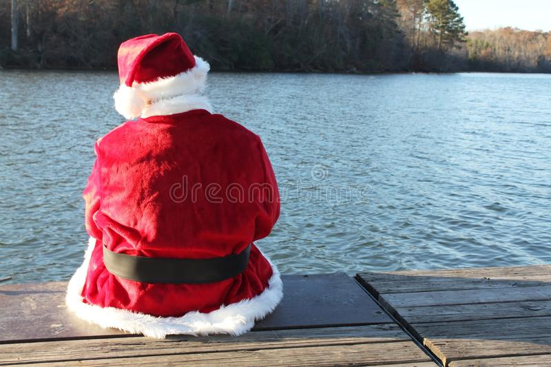 Santa Resting on the Dock. Santa taking a break sitting on the edge of a dock by a beautiful lake stock photography