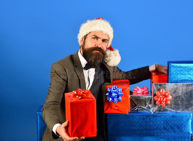 Santa in retro suit presents blue and red gifts. royalty free stock image