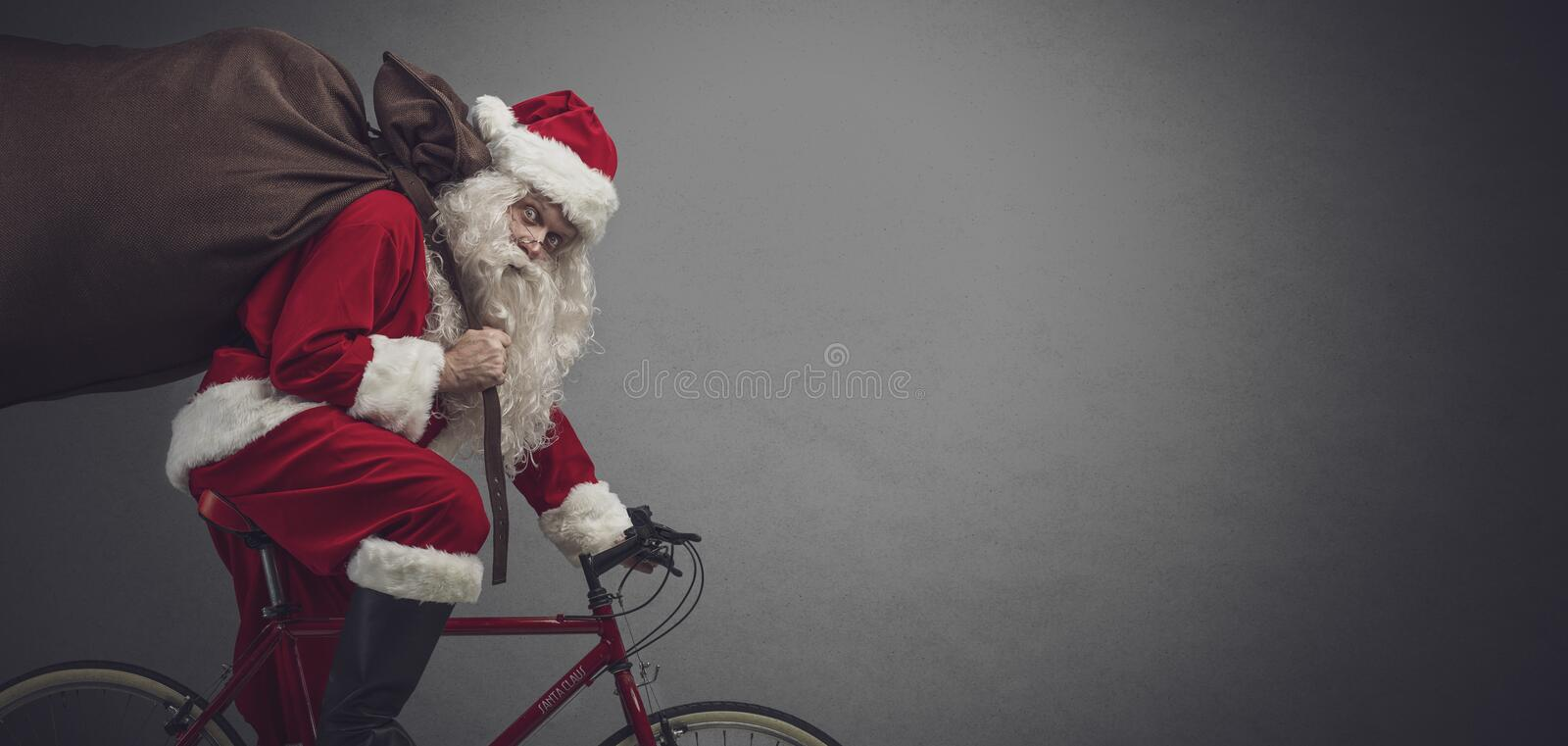 Santa riding a bicycle and carrying gifts. Santa Claus carrying a heavy sack with gifts for Christmas and riding a bicycle, banner with blank copy space stock photography