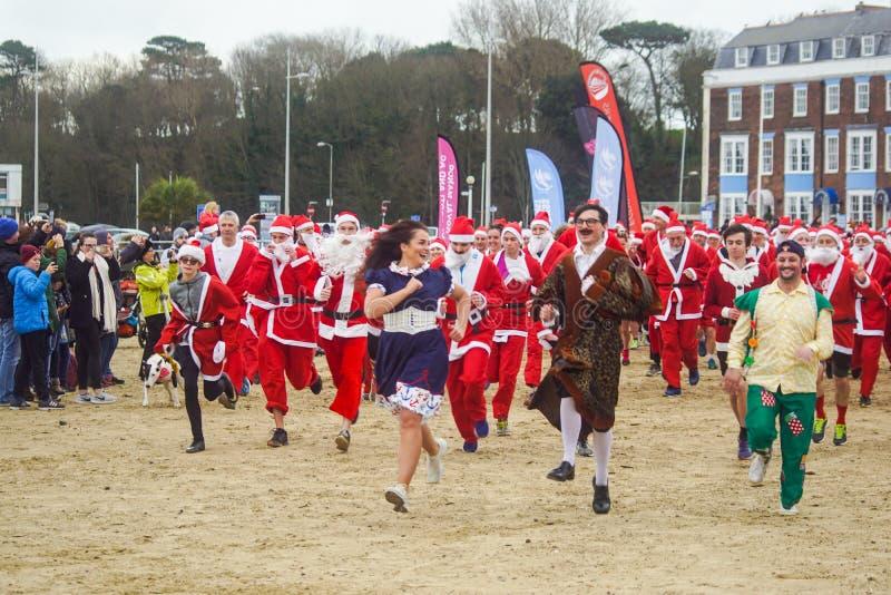 Santa Run sur la plage de Weymouth ayant l'amusement images stock