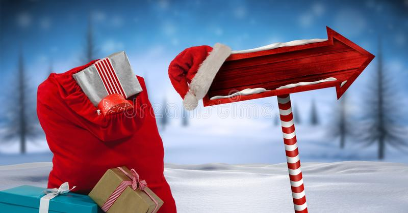 Santa`s bag with gifts and Wooden signpost in Christmas Winter landscape and Santa hat royalty free stock photography