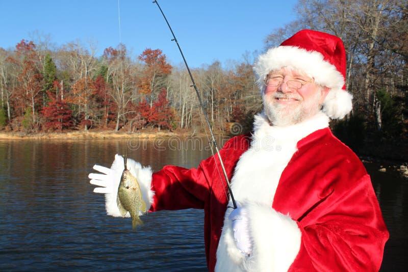 Santa's Big Clatch 2. Santa proudly holding the fish caught on his last break before the big Christmas rush stock photo