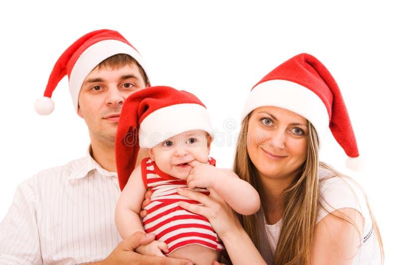 Santa's family. Happy family in santa's hats celebrating christmas. Isolated over white