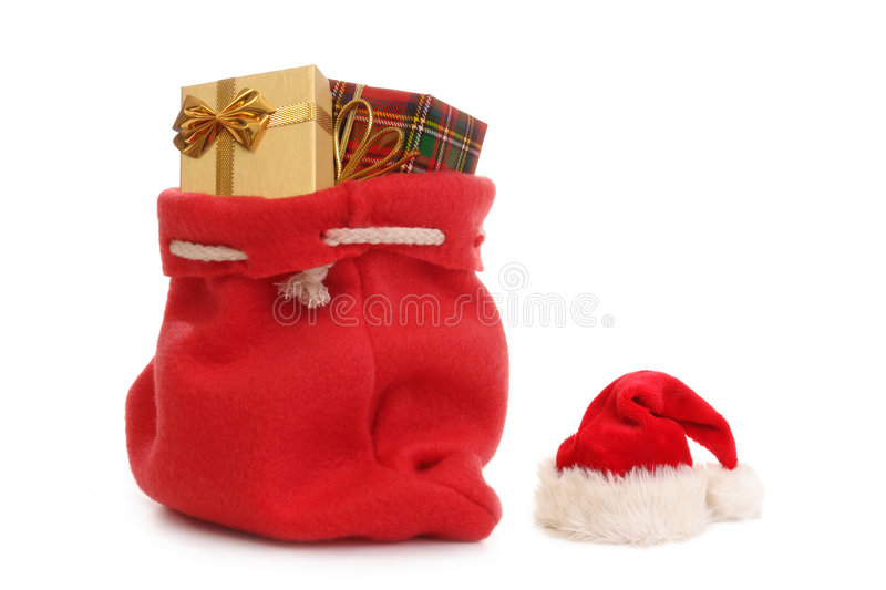 Santa's gifts. Red Santa Claus hat and bag full of christmas presents over white background royalty free stock photography