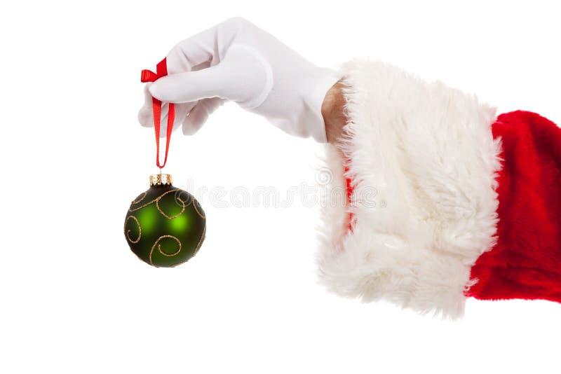 Santa's hand holding a green Christmas ornament stock photo