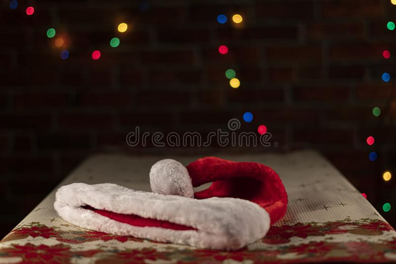 Santa`s hat on a Christmas table with an unfocused light background on a brick wall. Christmas Concept royalty free stock image