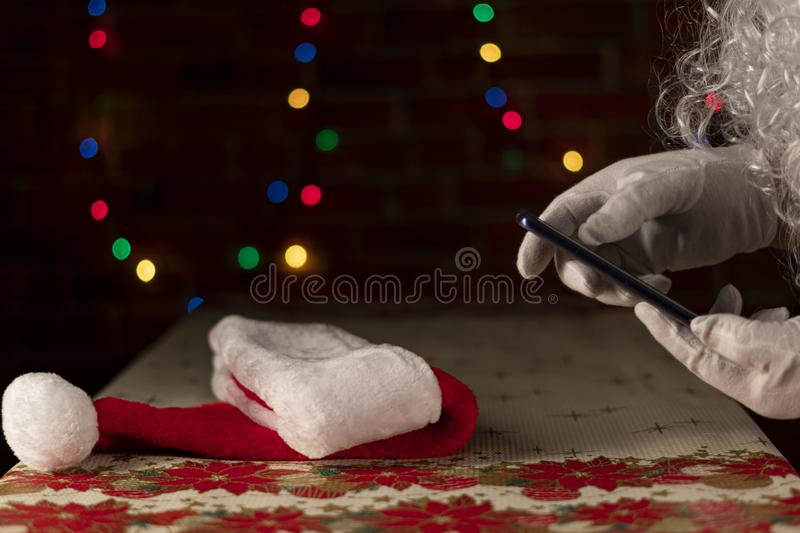 Santa`s hat on a Christmas table with an unfocused light background on a brick wall. Santa Claus consulting the smart phone. royalty free stock image
