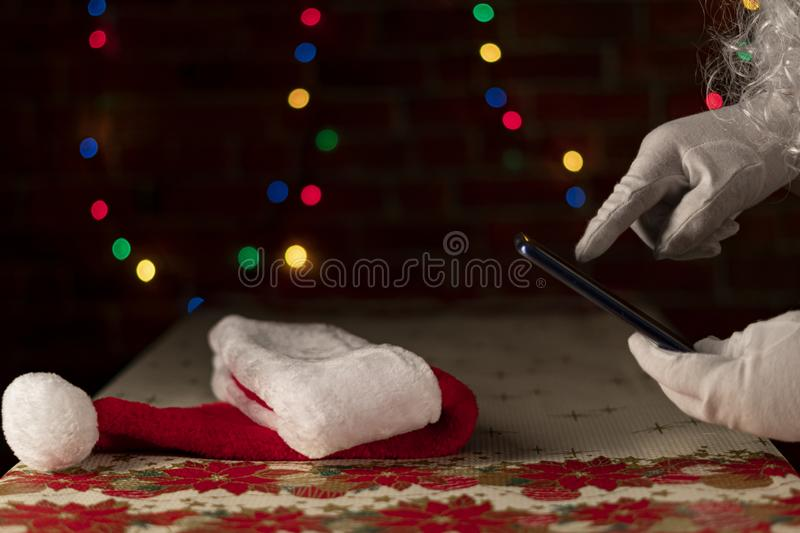 Santa`s hat on a Christmas table with an unfocused light background on a brick wall. Santa Claus consulting the smart phone. royalty free stock photography