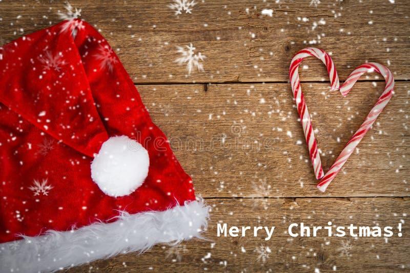 Santa& x27; s-hatt och godisrotting på träbakgrund arkivbild