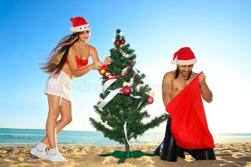 Santa's helper and Santa at the tropical beach royalty free stock image