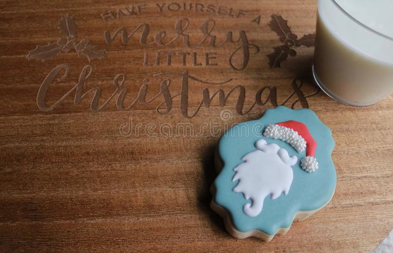 Christmas milk and sugar cookie on Have Yourself a Merry Little Christmas wooden board royalty free stock photos