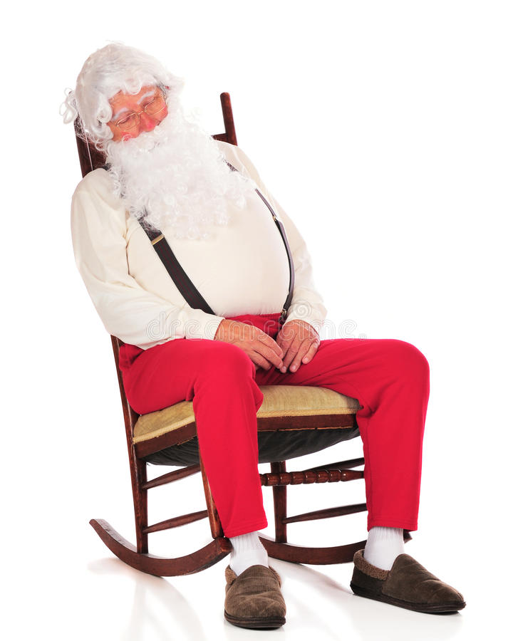 Santa's Snooze. Santa snoozing in his rocker after a hard day in the toy shop. Isolated on white stock images