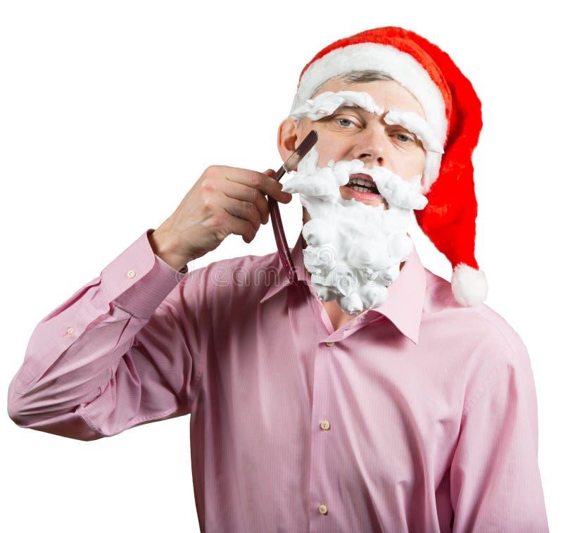 Santa shaving his foam beard. Man in Santa hat shaving his foam beard by cutthroat blade. Isolated on white royalty free stock images