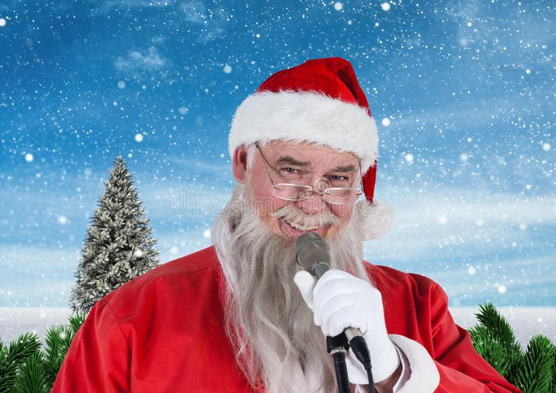 Santa singing christmas song on microphone. Portrait of santa singing christmas song on microphone against digitally generated snowy background stock image