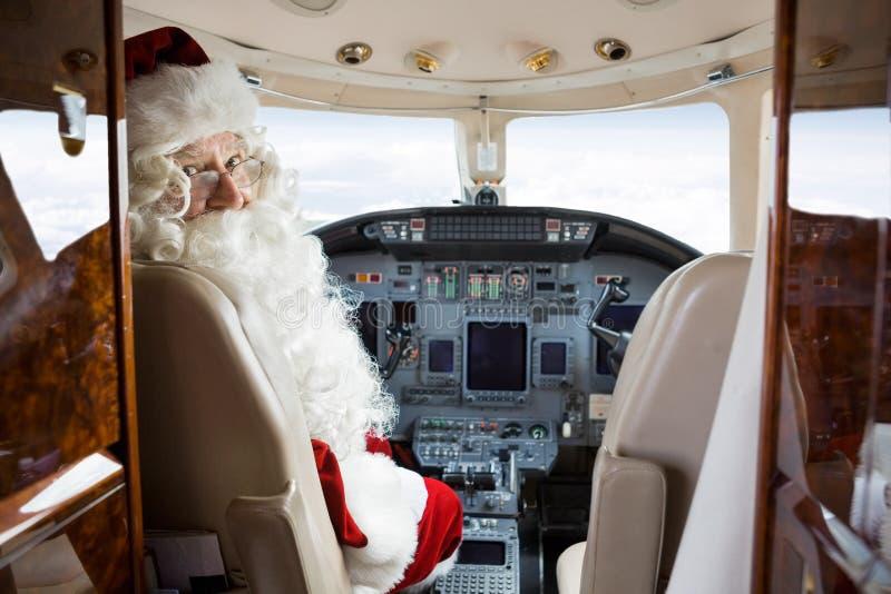 Santa Sitting In Cockpit Of privat stråle royaltyfria bilder