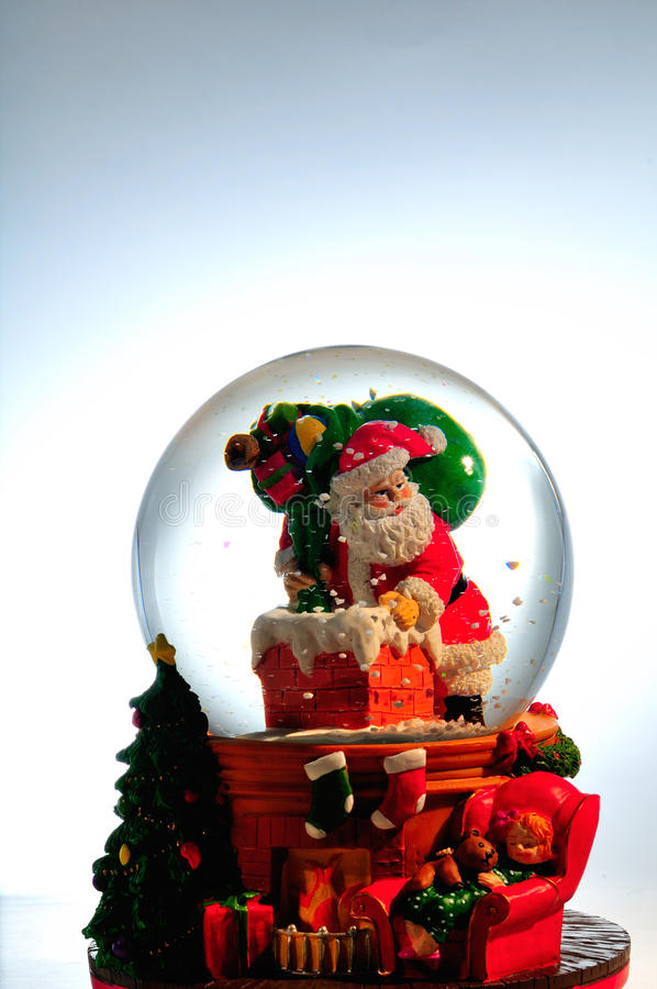 Santa snow globe. A Christmas snow globe with Santa Claus climbing into a chimney with a bag of toys royalty free stock photo