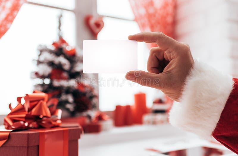 Santa tenant une carte de visite professionnelle de visite photos stock