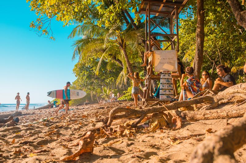 Santa Teresa, Costa Rica - June, 28, 2018: Toursist sirtring in the sand and enjoying the beautiful view of Santa Teresa. Beach, and some surfers check out the stock images