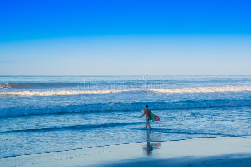 Santa Teresa, Costa Rica - June, 28, 2018: Young teen walking in the shore of the beach of Santa Teresa with his. Surfboard ready to surf in a beautiful sunny stock image