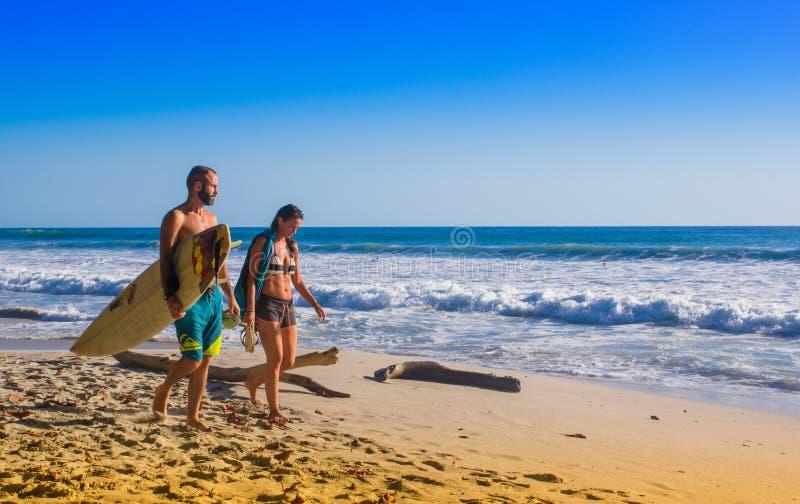 Santa Teresa Costa Rica - Juni, 28, 2018: Par av surfare på stranden av Santa Teresa som går och tycker om tiden arkivfoto