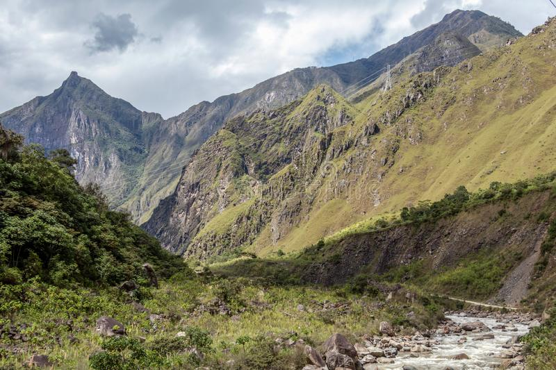 The Santa Teresa River in green lush valley. Hiking trail to Machu Picchu, Peru. Suspended bridge hanging above the Santa Teresa River in green lush valley stock images