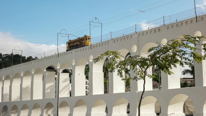 Santa teresa tram crossing lapa arches in rio de janeiro. Low angle shot of the santa teresa tram crossing the lapa arches in rio de janeiro, brazil royalty free stock images