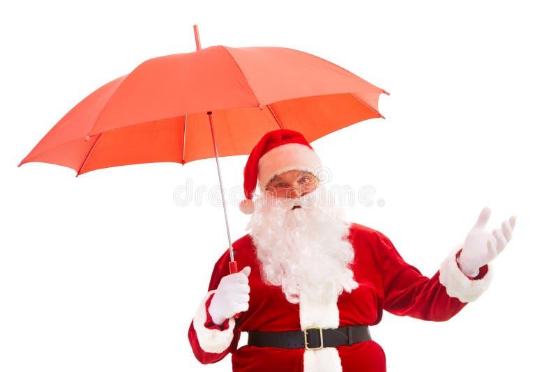 Santa with umbrella. Photo of happy Santa Claus with red umbrella in isolation stock photos