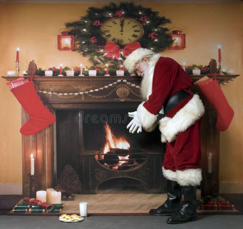 Santa Warming By The Fireplace royalty-vrije stock foto's