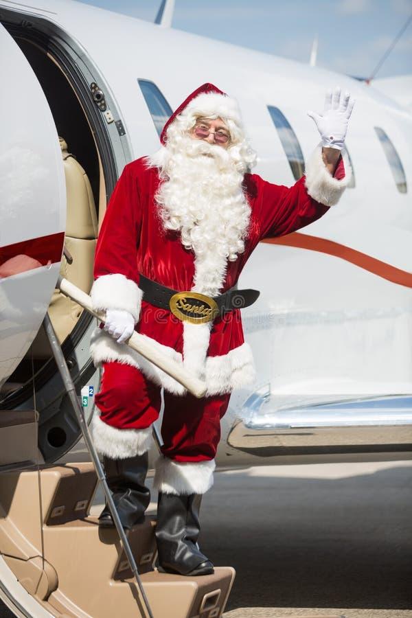 Santa Waving Hand While Standing en el jet privado imagen de archivo