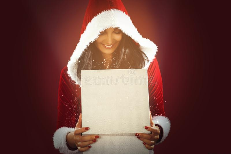 Santa woman in hat opening a magical box with present,red background. stock photo