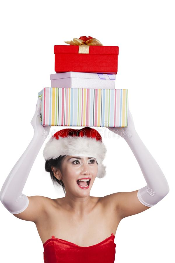Santa woman holding Christmas gifts over her head stock image