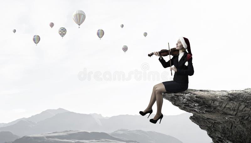 Santa woman play violin royalty free stock photography