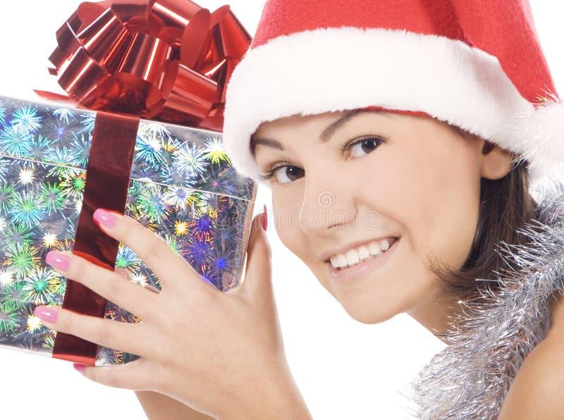 Woman showing gift wearing Santa hat royalty free stock photography