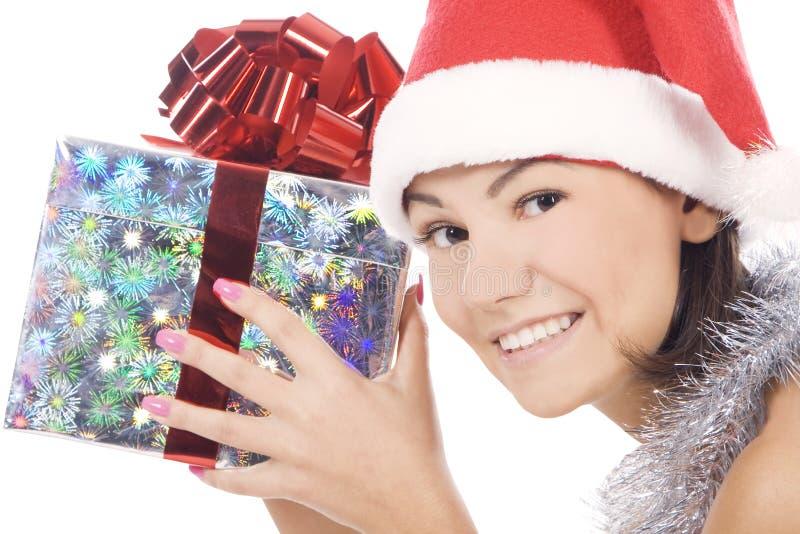 Santa woman showing gift wearing Santa hat. stock images