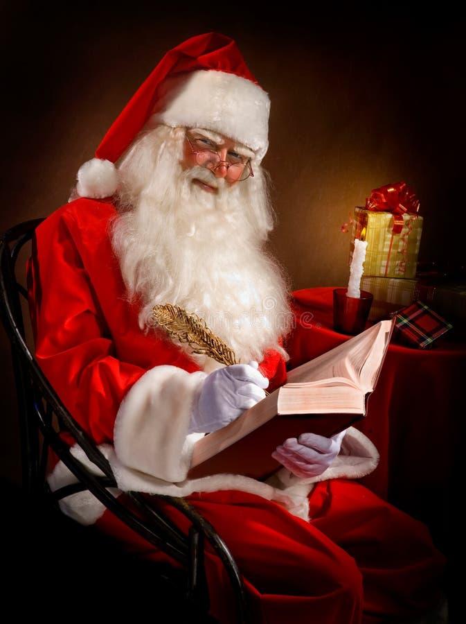 Santa Writes une plume magique dans le livre photos stock