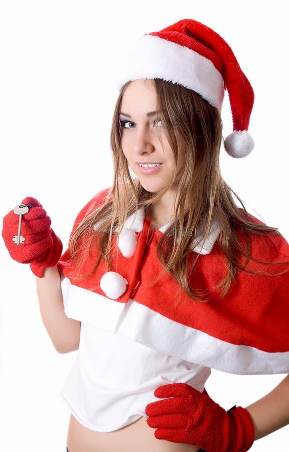 Santa young girl in Christmas hat gives car key royalty free stock image