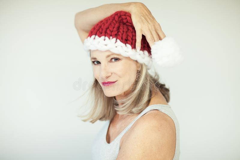 Santas λίγος αρωγός Όμορφη ευτυχής ανώτερη γυναίκα με ένα καπέλο Άγιου Βασίλη στοκ φωτογραφία με δικαίωμα ελεύθερης χρήσης