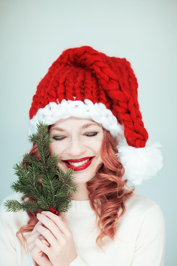 Santas λίγος αρωγός Όμορφη ευτυχής νέα γυναίκα με ένα καπέλο Άγιου Βασίλη στοκ φωτογραφία