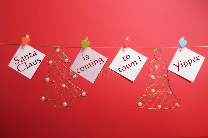 Santas Claus is Coming to Town. Message written on hanging signs with pegs from Christmas ornament line against a festive holiday red background stock image