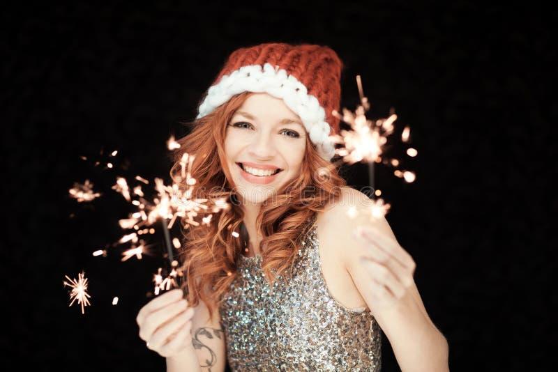 Santas Mały pomagier Piękna szczęśliwa młoda kobieta z Santa Claus kapeluszem, perfect uzupełniał, czerwona pomadka, trzyma spark zdjęcia royalty free