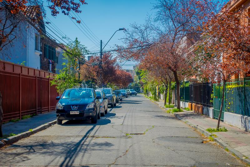 SANTIAGO, CHILE - SEPTEMBER 13, 2018: Outdoor view of some cars circulating in the streets with a greet traffict light. Surrounding of trees at each side of royalty free stock image
